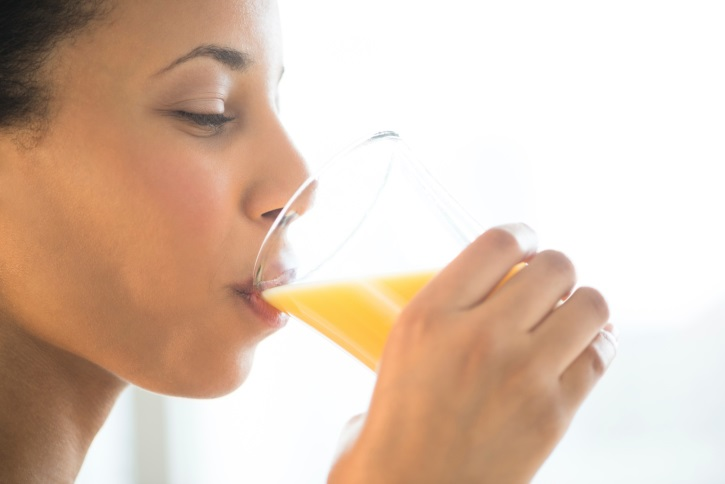Close-Up Of Woman Drinking Orange Juice